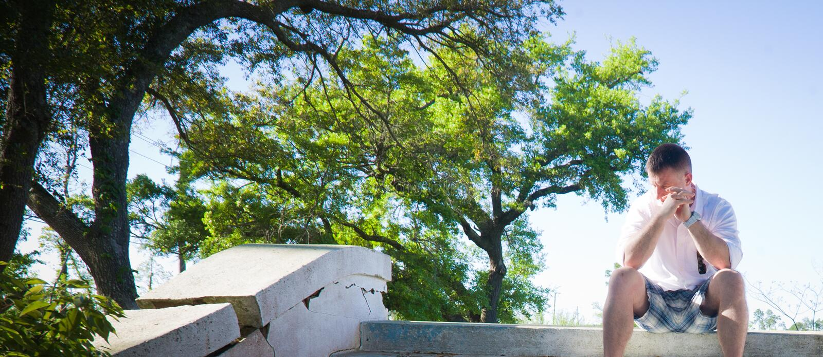 A Man Alone. A man sitting alone on crumbling steps with oak trees and blue sky in the background stock photo