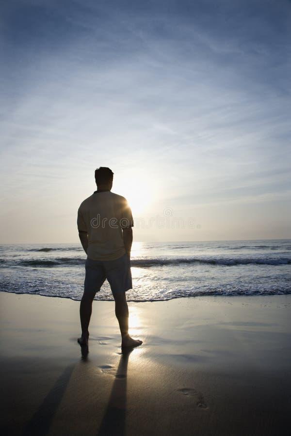 Man alone on beach. stock photos