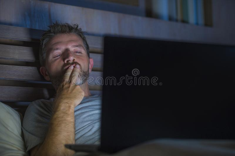 Man alone in bed playing cybersex using laptop computer watching sex movie late at night with lascivious pervert face. Young aroused man alone in bed playing royalty free stock images