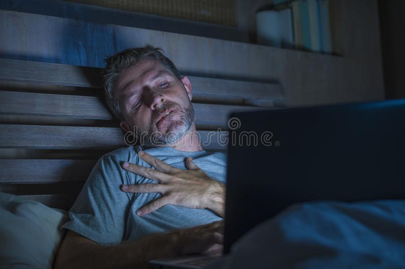 Man alone in bed playing cybersex using laptop computer watching sex movie late at night with lascivious pervert face. Young aroused man alone in bed playing stock image