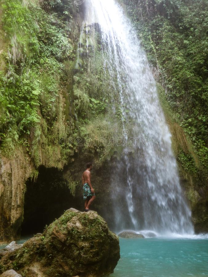 Man alone in deep forest waterfall, inambakan falls in Cebu Island in Philppines. Epic man alone in deep forest waterfall from mountain gorge at hidden tropical royalty free stock photo