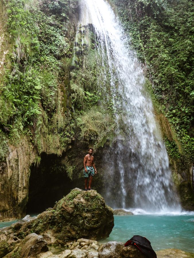 Man alone in deep forest waterfall, inambakan falls in Cebu Island in Philppines. Epic man alone in deep forest waterfall from mountain gorge at hidden tropical stock images