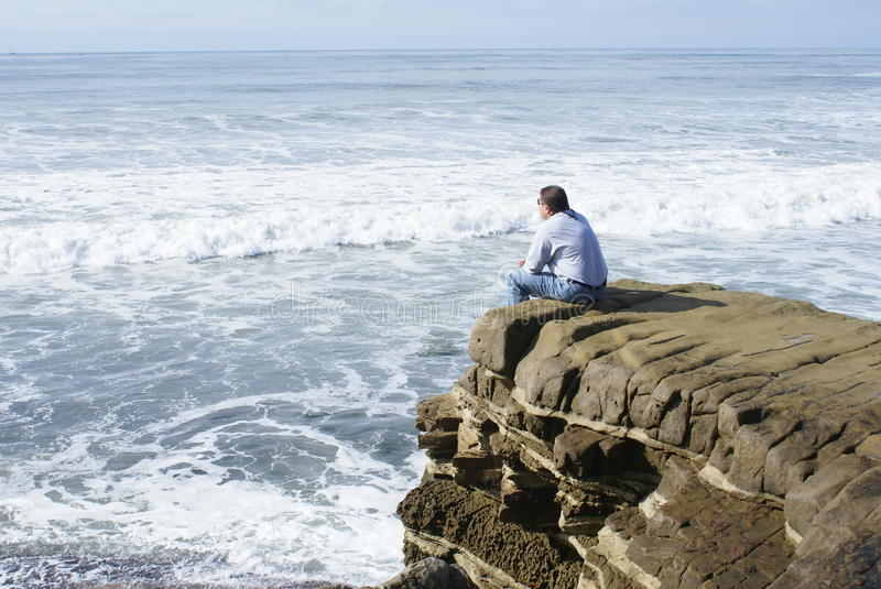 Man Alone Meditating or Thinking. Man sitting all alone on a rock in California, United States overlooking the ocean meditating or thinking royalty free stock photos