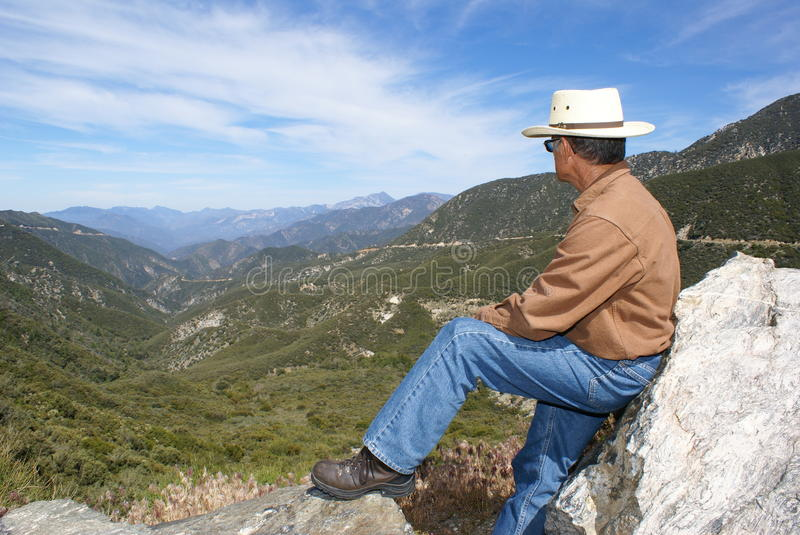 Man Alone Meditating or Thinking. Man sitting on a large boulder alone overlooking a canyon in the Angeles National Forest, in Southern California meditating or stock photo