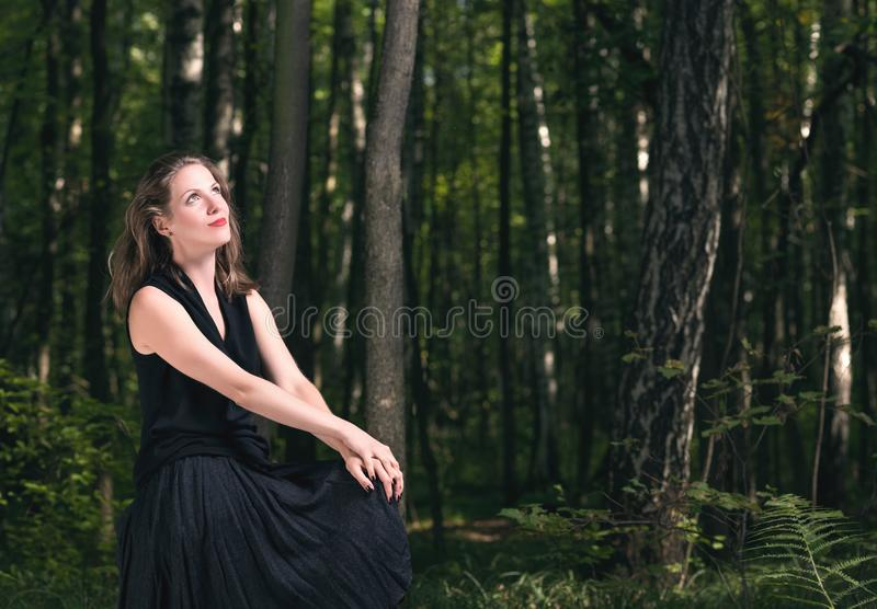 Man alone with nature forest. Portrait of a young woman in a black dress sitting in the woods stock images