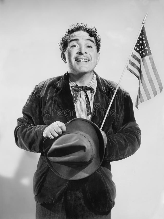 Man with the American flag in his hand smiling. (All persons depicted are no longer living and no estate exists. Supplier grants that there will be no model stock image