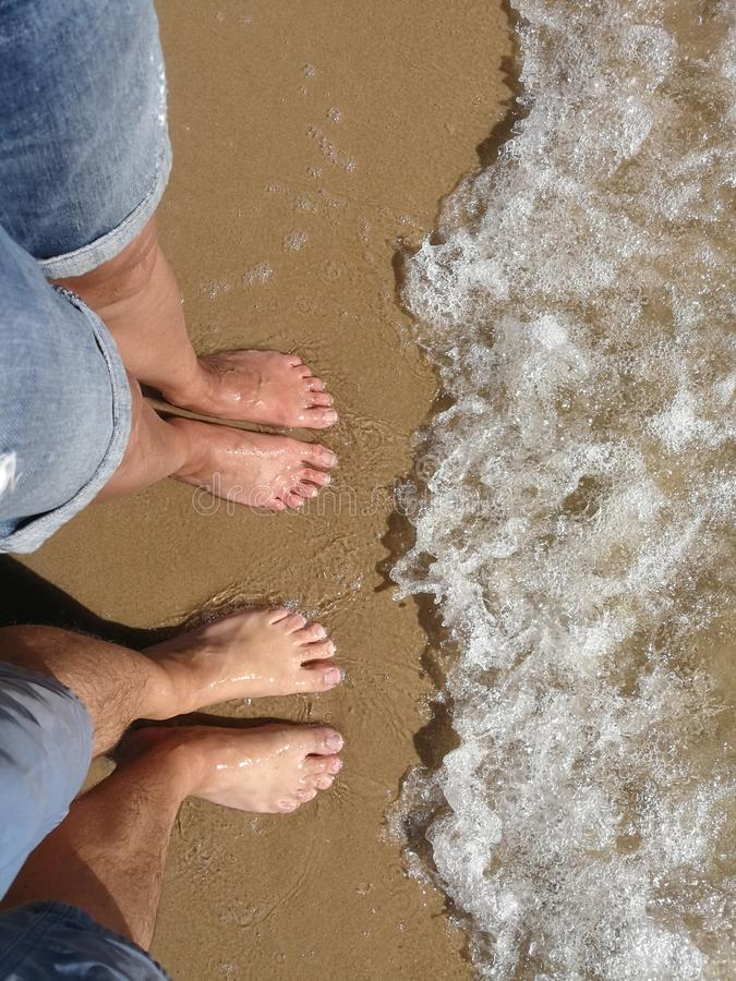 Free Man And Woman Stand With Their Feet On The Beach Stock Photography - 123235862