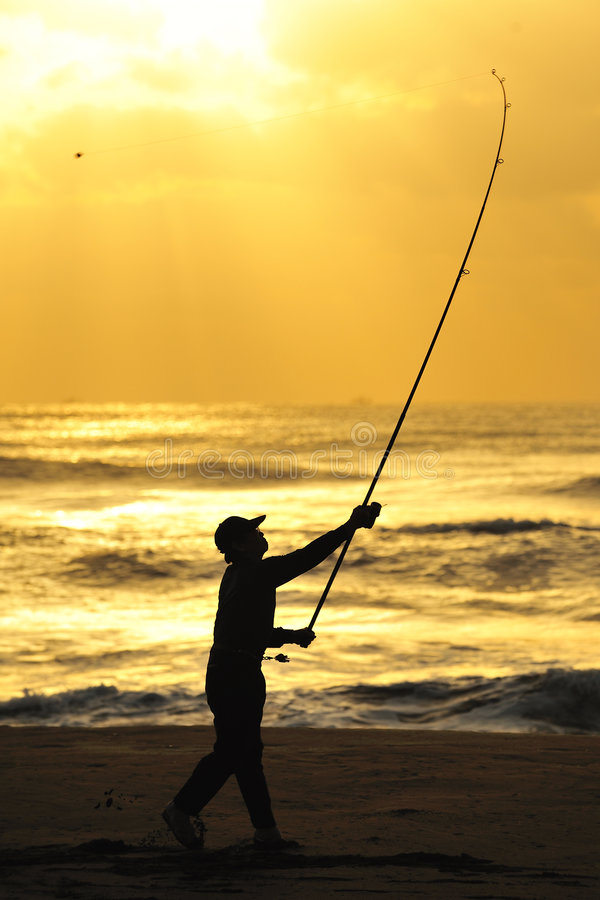 Man Angling in the Dawn. A man angling by the beach in the dawn stock photo