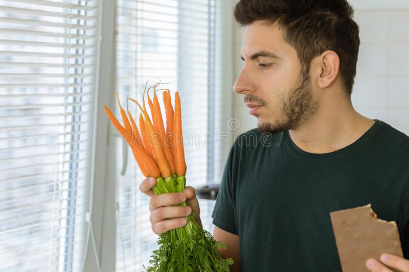 The man is angry and upset, he does not want to eat vegetables. He wants to eat chocolate stock photo