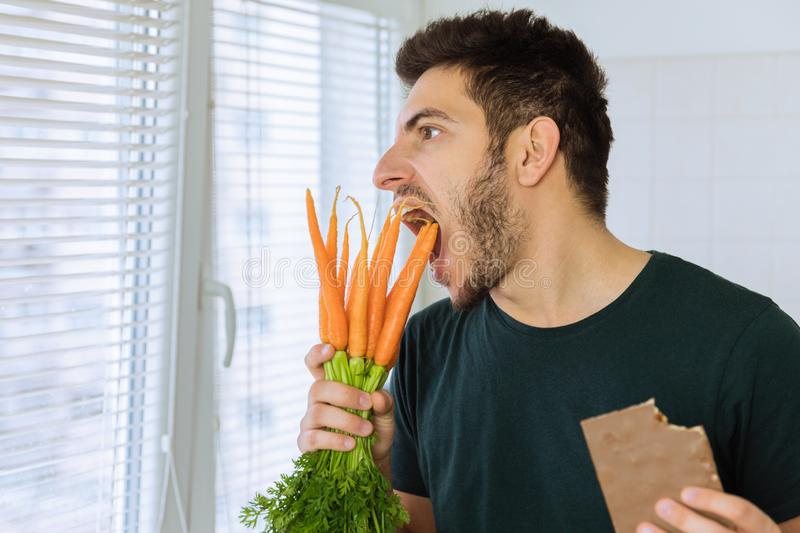 The man is angry and upset, he does not want to eat vegetables. He wants to eat chocolate stock photography