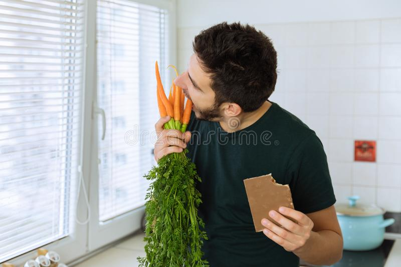 The man is angry and upset, he does not want to eat vegetables. He wants to eat chocolate royalty free stock photos