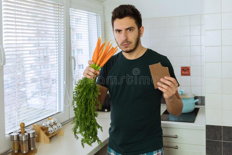 The man is angry and upset, he does not want to eat vegetables. He wants to eat chocolate royalty free stock image