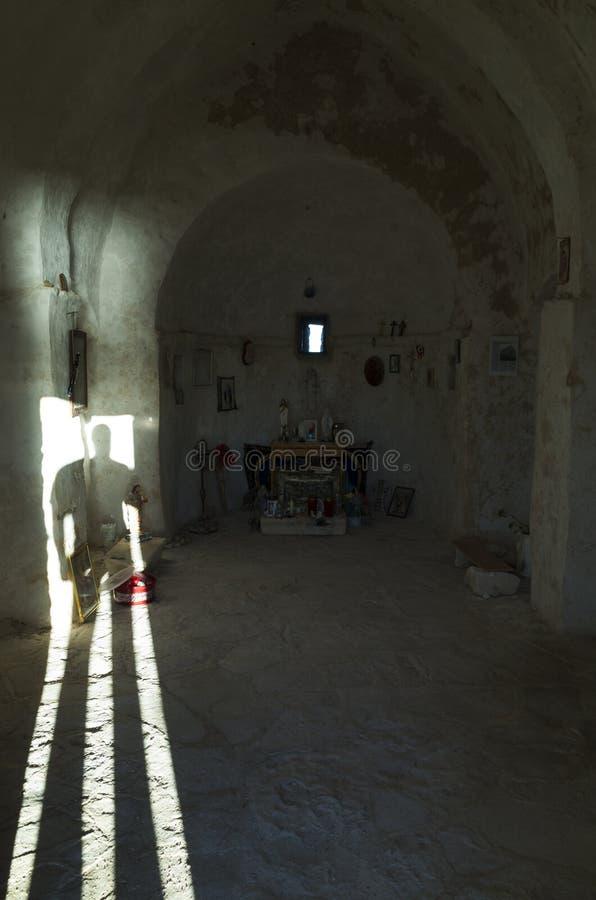 Man anseendet i väg för öppen dörr med ljust skina in i liten kyrka arkivfoto