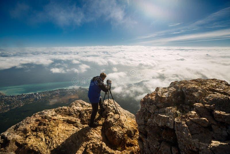 Man anseendet med en tripod och kameran på ett maximum för högt berg ovanför moln, stad och havet Yrkesmässig fotograf royaltyfri fotografi