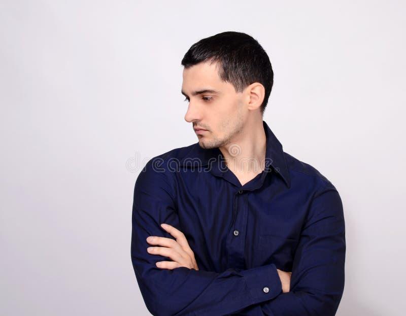 Man anseendet med hans armar korsade se ner över skuldran till sidan från profil. royaltyfri bild