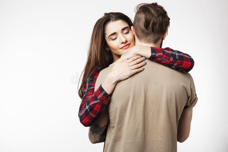 Man anseendet med tillbaka till kameran, flickvännen som romantiskt kramar honom royaltyfria foton