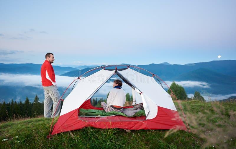 Man anseendet nära tältet som sitter i kvinnan mot härligt landskap av väldiga berg arkivfoto