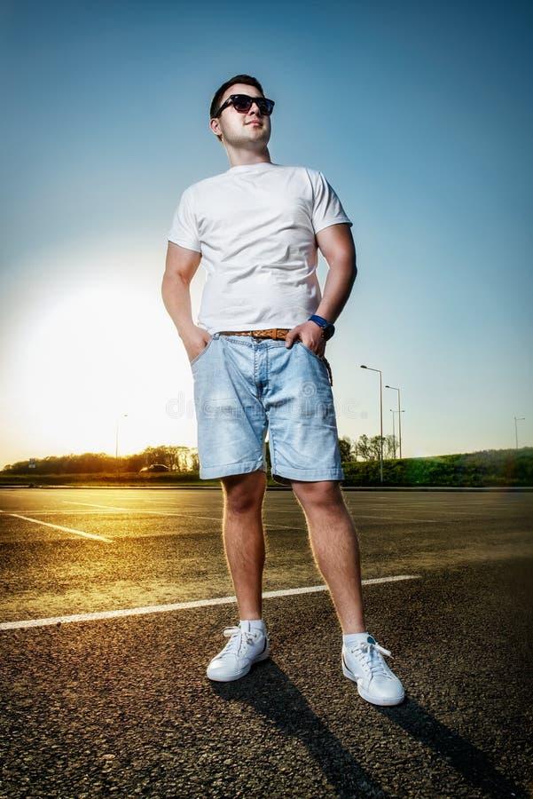 Man anseendet på asfaltvägen på solnedgången royaltyfri foto