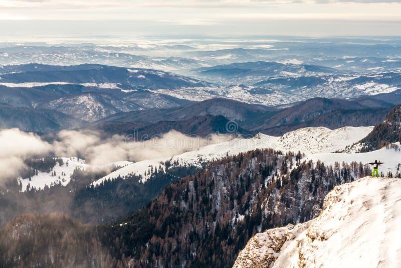 Man anseendet på en klippa, ovanför molnen som känner sig kraftiga som är lyckade arkivbilder