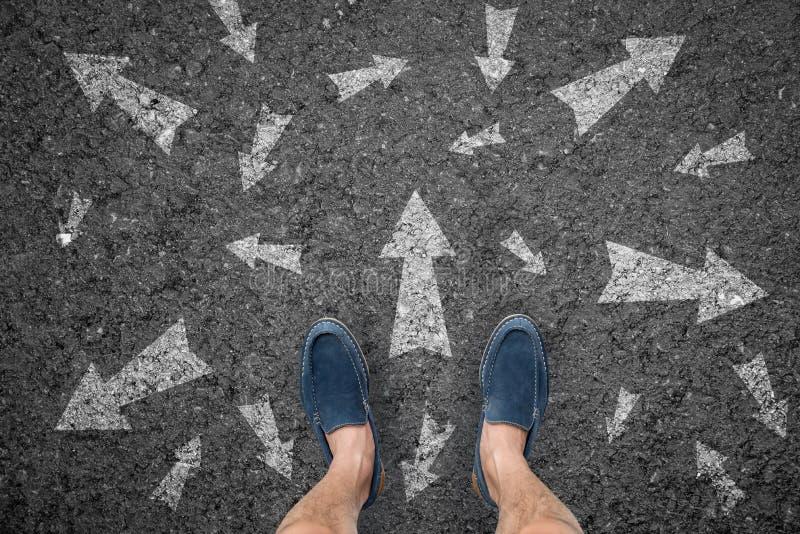 Man anseendet på vägen med många riktningspilval eller flytta sig royaltyfri foto