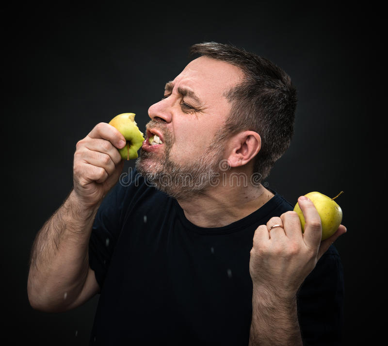 Man with an appetite eating a green apple royalty free stock image