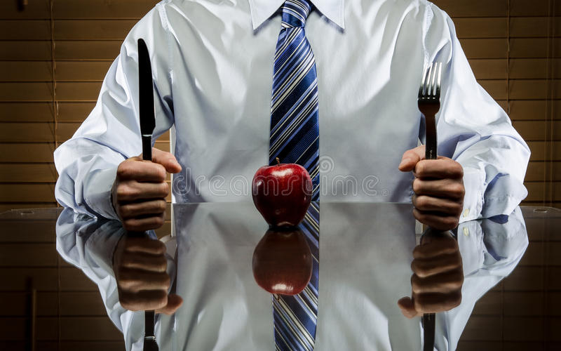 Man with an apple and cutlery stock photography
