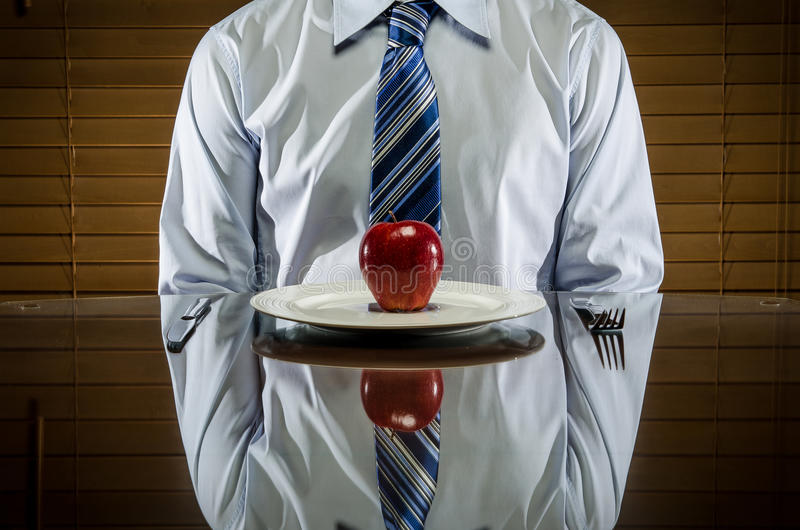 Man with apple on a plate stock photos