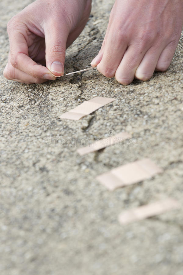 Man Applying Adhesive Bandage On Cracked Road. stock photo