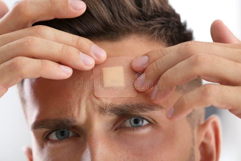 Man applying adhesive bandage on forehead indoors. Closeup royalty free stock images