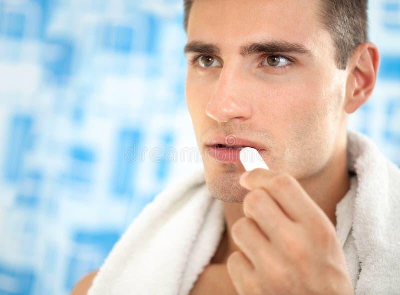 Man applying balsam for lips. Handsome man applying balsam for lips, care of lips royalty free stock photos