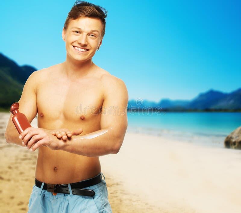 Man applying cream on a beach stock image