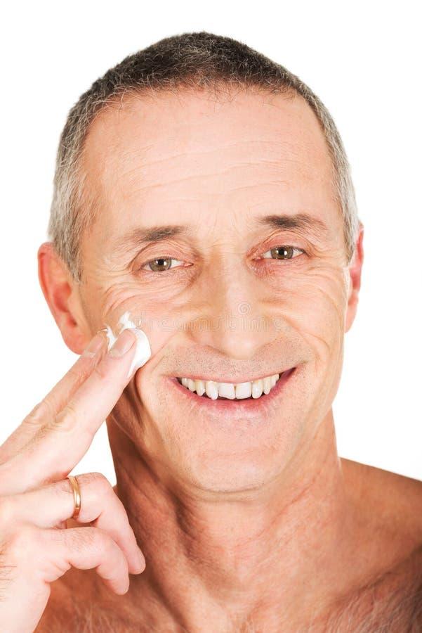 Mature man applying face cream eyes closed closeup bildbanksbilder