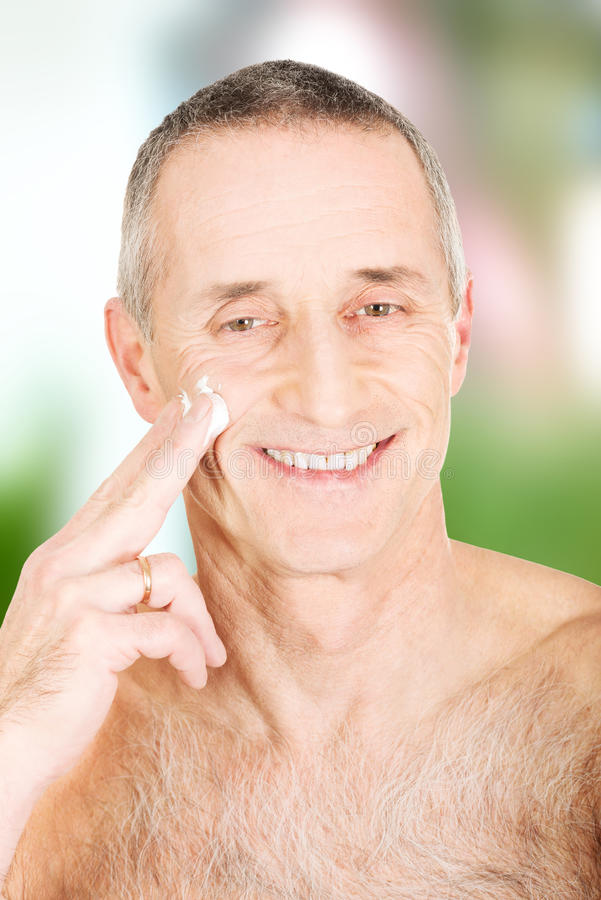 Man applying cream on his face royalty free stock images