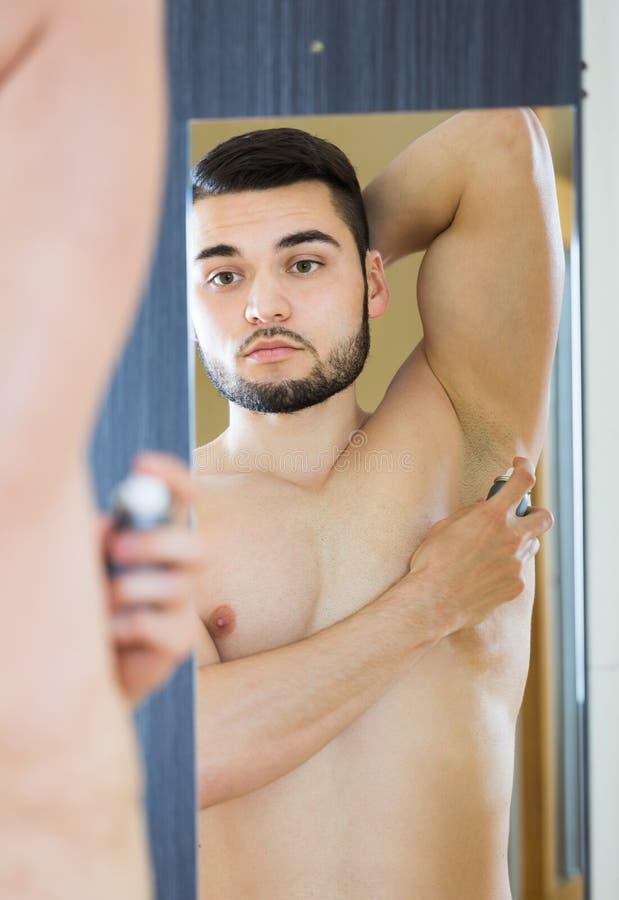 Man applying deodorant. Handsome man applying deodorant at home royalty free stock photography