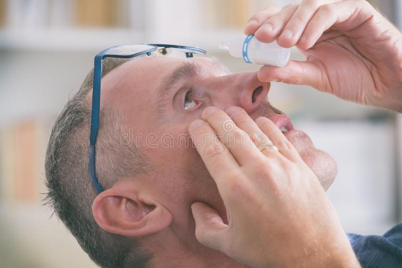 Man applying eye drops royalty free stock photo