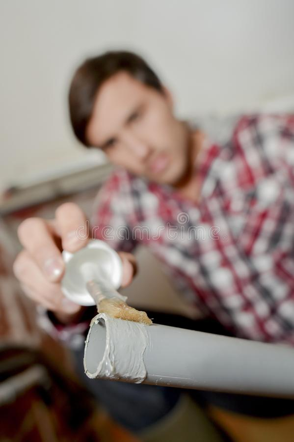 Man applying glue to end pvc pipe royalty free stock photography