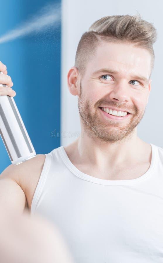 Man applying hair spray. Portrait of handsome man applying hair spray royalty free stock image
