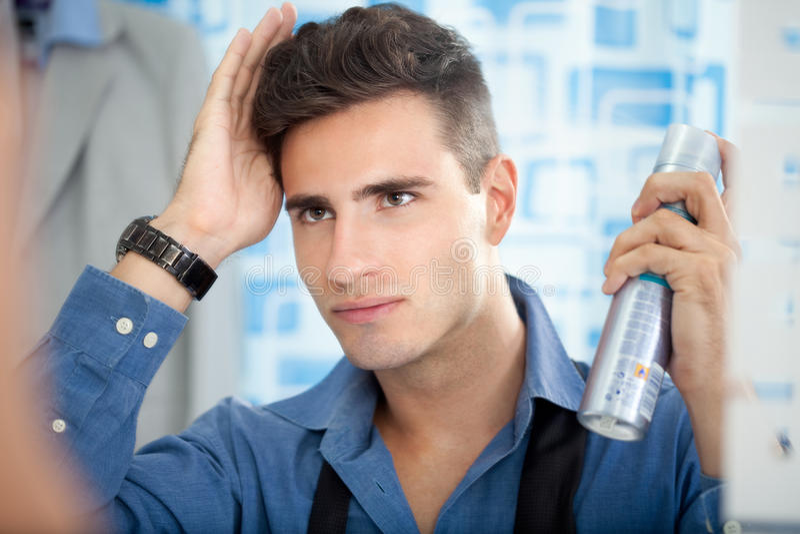Man applying hair spray. Young man applying hair spray to his hair stock photos