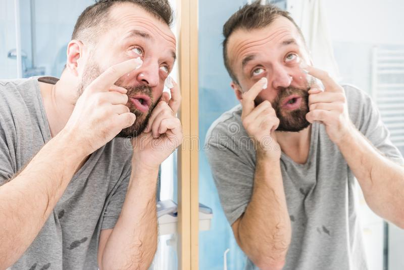 Man Applying Moisturizer Cream In Bathroom Stock Image