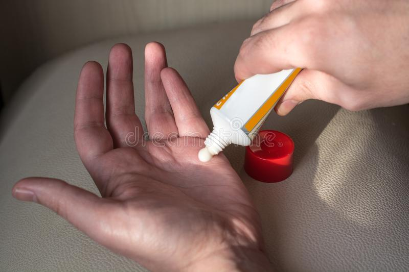 Man applying the ointment from the tube. royalty free stock photography