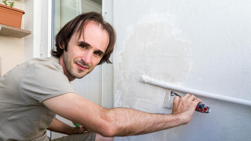 Man applying plaster mix on the wall with spatula. DIY concept. royalty free stock image