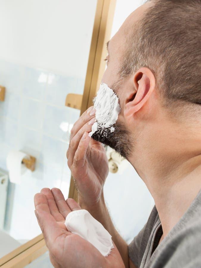 Man applying shaving cream on beard royalty free stock image