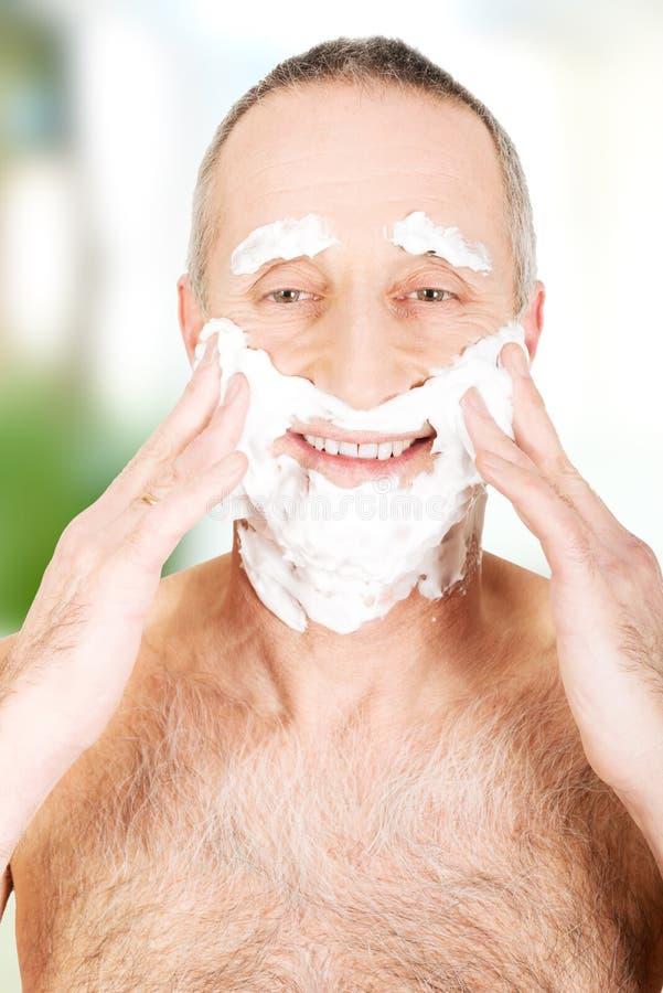 Man applying shaving foam stock images