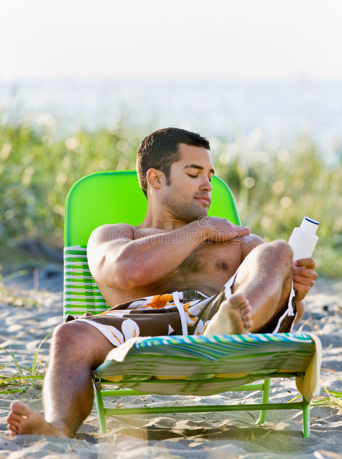 Download Man Applying Sunscreen Lotion At Beach Stock Photo - Image: 7430780