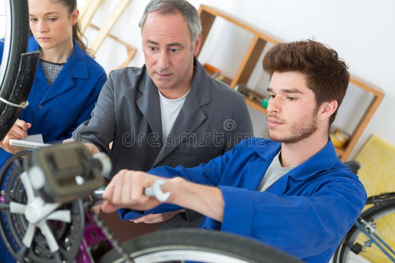 Man and apprentices in bike mechanics in workshop. Man stock images