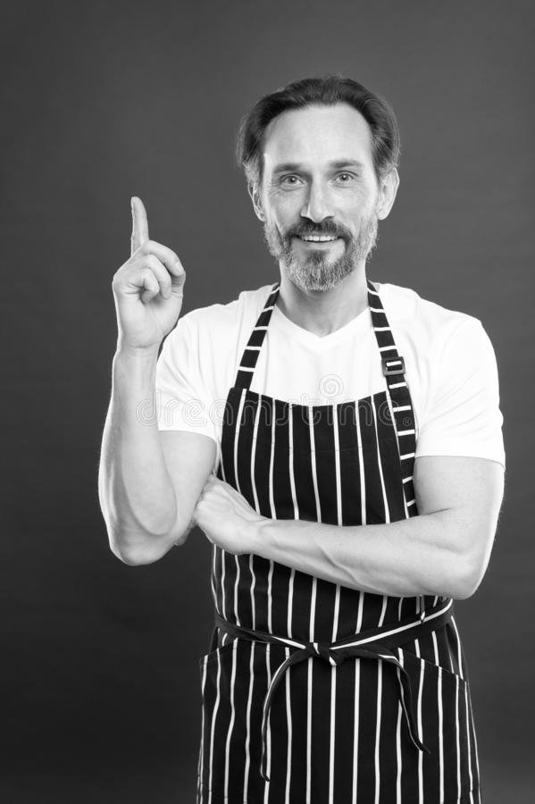 Man in apron. Confident mature handsome man in apron red background. He might be baker gardener chef or cleaner. Good in. Everything. Multitasking and stock image