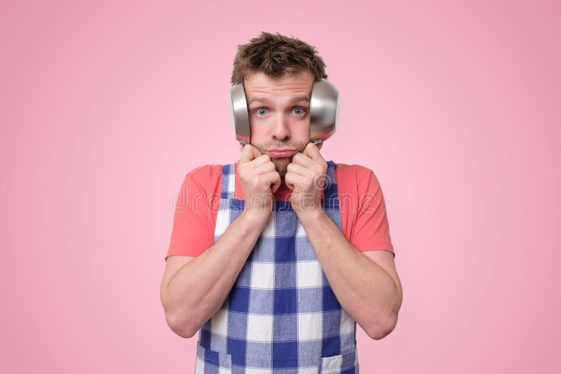Man in apron covering his ears with pans. royalty free stock image
