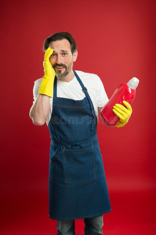 Man in apron with gloves hold plastic bottle liquid soap chemical cleaning agent. Cleaning day today. Bearded guy. Cleaning home. Cleanliness and order stock image