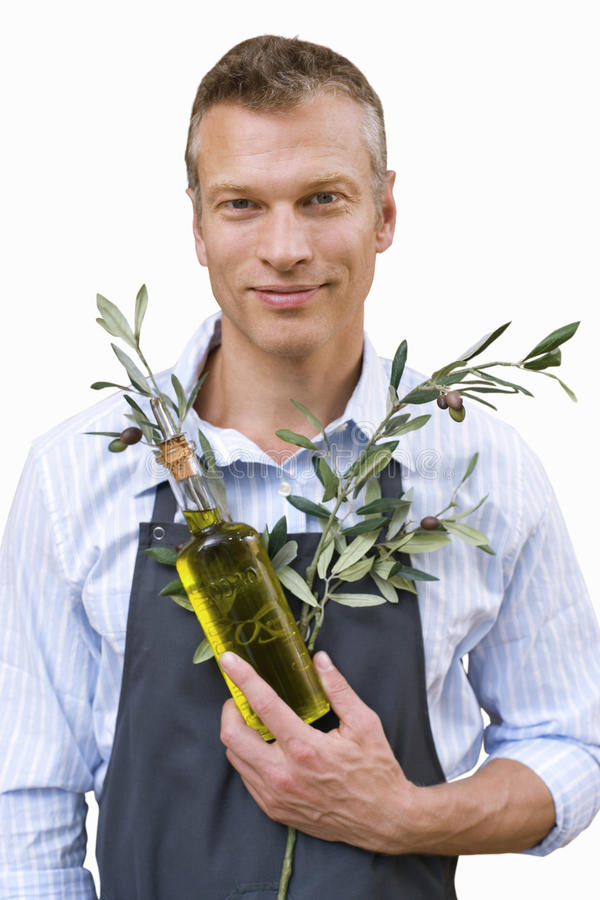 Man with apron holding olive branches and bottle of oil, cut out stock photography