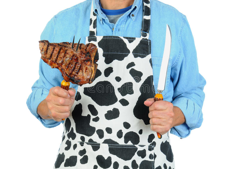 Man in Apron with Steak on Fork stock photography
